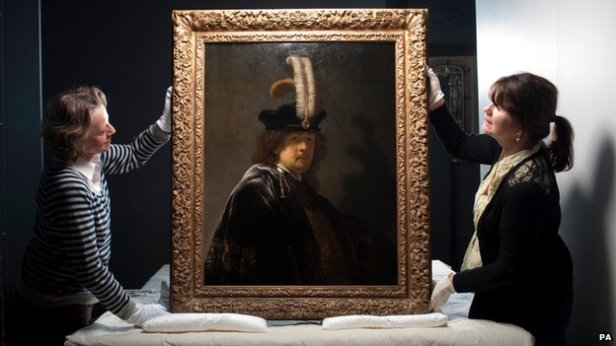 (Preservationists display the cleaned and authenticated Rembrandt self-portrait.  Image Credit:PA/BBC)