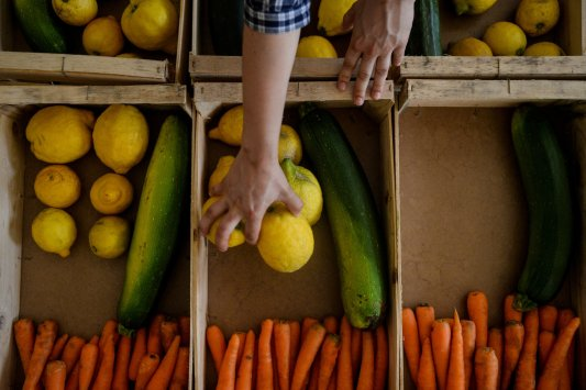 (A volunteer organizes the food crates at a distribution center. Image Credit:)